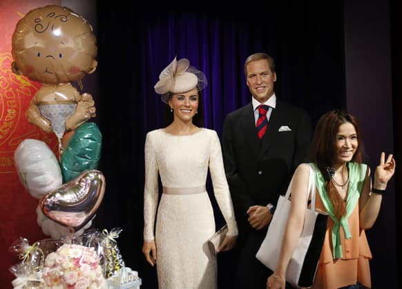 A visitor poses for a picture with wax figures of Britain`s Prince William and wife Kate as balloons are displayed in celebration of the birth of the couple`s first child, at Madame Tussauds in Tokyo.