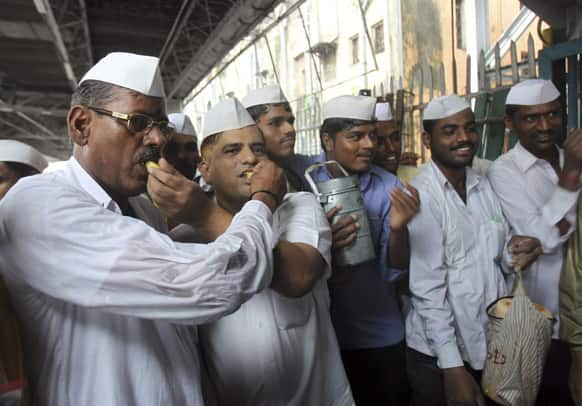 Dabbawalas, or lunchbox delivery men, pass out sweets in celebration of the birth of the Prince of Cambridge, the son of Britain`s Prince William and Kate, Duchess of Cambridge, at a railway platform in Mumbai.