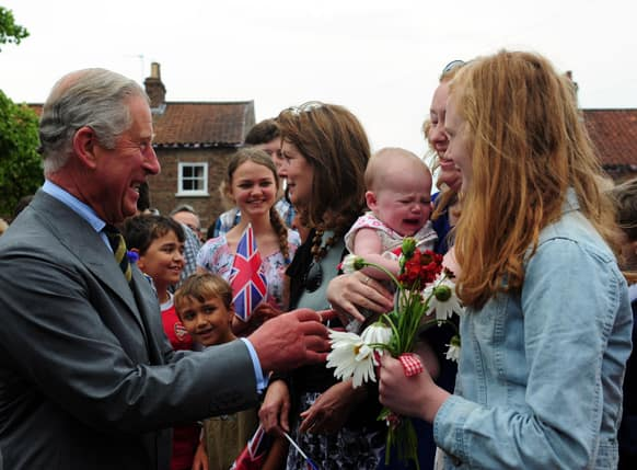 Britain`s Prince Charles, the Prince of Wales, with 6 month old Emily Scott, as he meets crowds of well wishers on a visit to Bugthorpe, England.