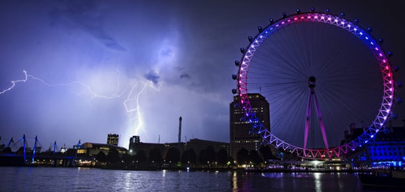 Lightning strikes behind The London Eye in central London which is lighted up in the national colors of red, white and blue to mark the birth of Prince William and his wife Kate`s first child.
