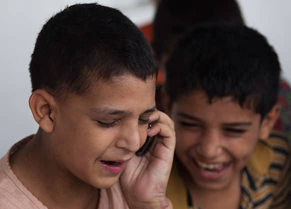 Pakistani runaway boy Naveed Khan talks to his father on the phone while waiting to go to his hometown Peshawar, at Edhi foundation shelter in Islamabad, Pakistan.