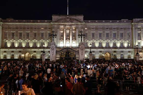 People gather outside a floodlit Buckingham Palace in London to mark the birth of a baby boy to Prince William and Kate, Duchess of Cambridge.