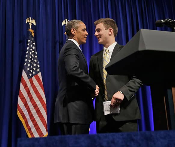 President Barack Obama, left, is introduced by Organizing for Action (OFA) field rep William Townsend, of Black Forest, Colo., before speaking at the event, in Washington.