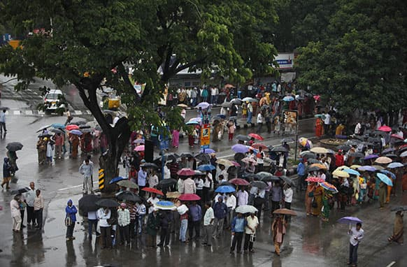 People hold umbrellas to protect themselves from the rain as they wait for buses in Hyderabad.