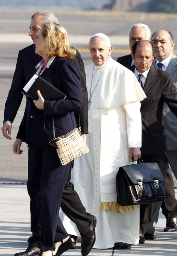 Pope Francis holds a bag at Rome`s Fiumicino international airport. It`s wheels up on Pope Francis` first trip abroad as pontiff.