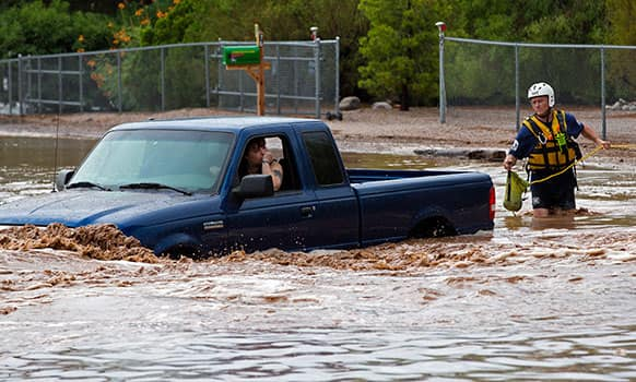 A man an woman sit in a truck on Tomahawk Rd. flooded by rain waters in Apache Junction, Ariz. Mesa Fire Dept. were able to walk the two out safely.