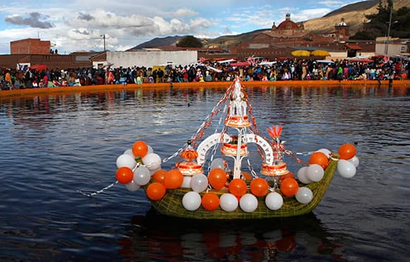 A boat made of reeds that grow in Titicaca Lake crarries cakes on a lagoon during a festival held in honor of Santiago the apostle, known as Saint James in English, the patron saint of the town in Guaqui, Bolivia.
