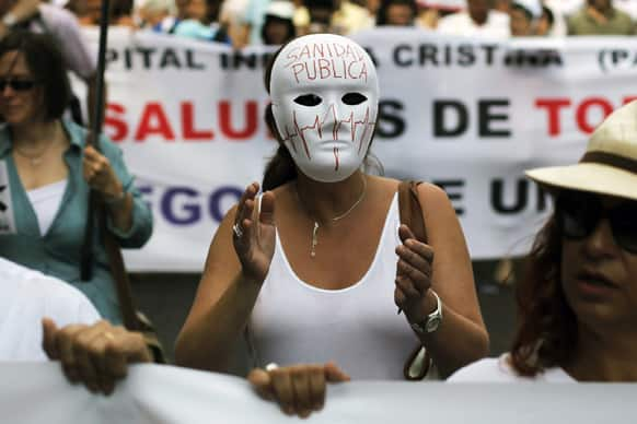 A protestor shouts slogans as she wears a mask reading