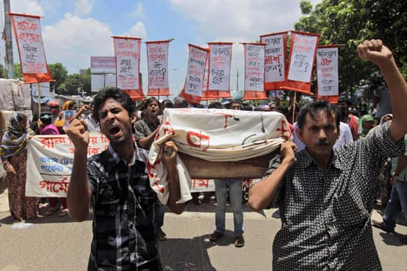 Bangladeshi activists, garment workers and relatives of victims participate in a protest with a symbolic coffin outside the Bangladesh Garment Manufacturers and Export Association (BGMEA) office building in Dhaka, Bangladesh.