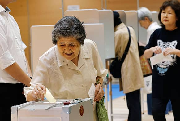 An elderly woman casts her vote in Japan`s upper house parliamentary elections at a polling station in Tokyo.