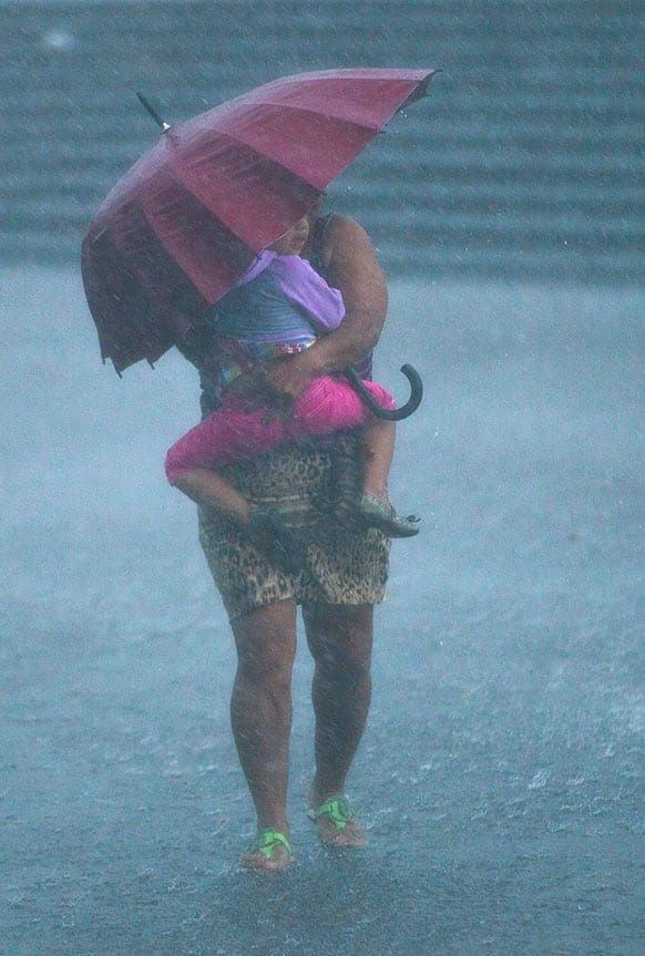 A woman carries a girl under an umbrella as it rains hard outside the Metropolitan Cathedral during a celebration honoring the
