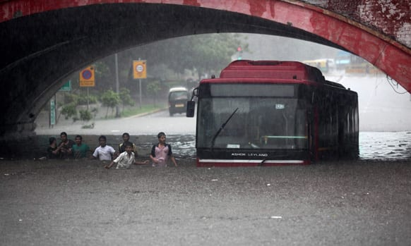 People wade past a bus submerged in rainwater in New Delhi. Heavy rainfall lashed the national capital Saturday, flooding streets and homes and choking the city with traffic jams.