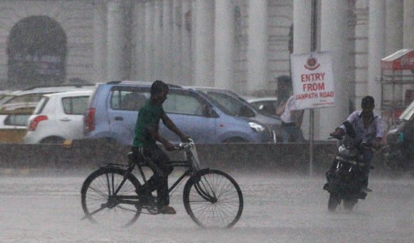 A cyclist pedals past a man riding a scooter during heavy rainfall in New Delhi. Heavy rainfall lashed the national capital Saturday, flooding streets and homes and choking the city with traffic jams.