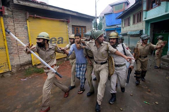 Police officer arrest a Kashmiri youth protesting during curfew in Srinagar.
