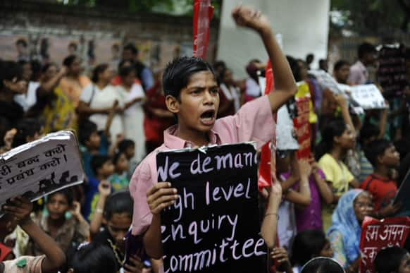 A boy shouts slogans, holding a placards during a protest organized by non-governmental organization Bachpan Bachao Andolan, or Save Childhood Movement, against the death of schoolchildren after eating free midday meal served at a school, in New Delhi.