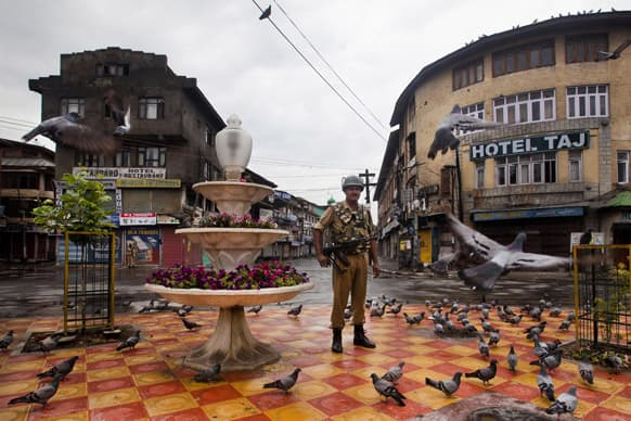 An Indian paramilitary soldier stands guard during curfew in Srinagar.