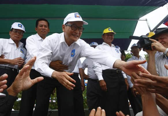 Sam Rainsy, center, president of the Cambodia National Rescue Party shakes hands with his party supporters during an election campaign at Kampong Speu province, west of Phnom Penh, Cambodia.