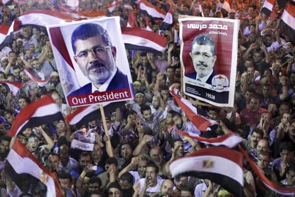 Supporters of Egypt`s ousted President Mohammed Morsi hold his posters and wave national flags as they protest in a park in front of Cairo University, where protesters have installed their camp in Giza, southwest of Cairo.