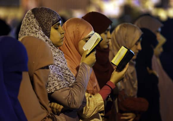 Supporters of Egypt`s ousted President Mohammed Morsi read verses from Islam`s holy book the Quran as they pray the Tarawih prayer, after the evening meal when Muslims break their fast during the Islamic month of Ramadan.