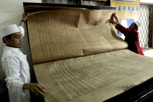 Teachers show a giant Quran displayed at Al-Ashriyyah Nurul Iman boarding school in Parung,West Java, Indonesia.