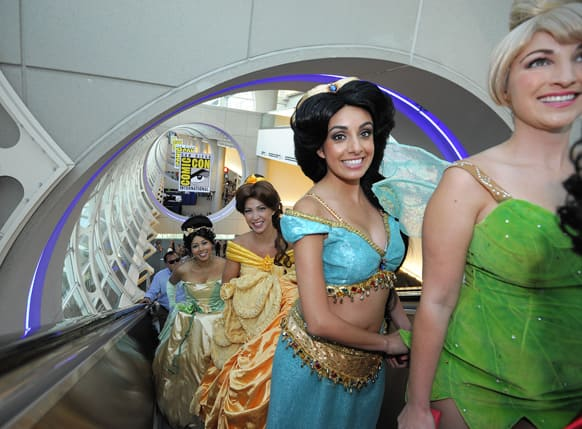 Fans dressed as Disney princesses ride the escalator as they get their credentials during the Preview Night event on Day 1 of the 2013 Comic-Con International Convention in San Diego, Calif.