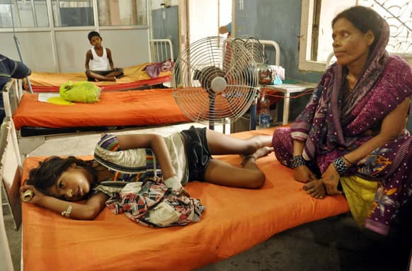 A woman sits beside a child who fell sick after eating a free school lunch, at a hospital in Patna.
