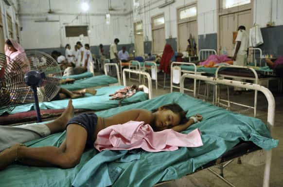 Children who fell sick after eating a free school lunch lie at a hospital in Patna.