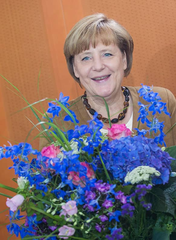German Chancellor Angela Merkel receives a bunch of flowers marking her 59th birthday prior to the weekly cabinet meeting at the chancellery in Berlin, Germany.