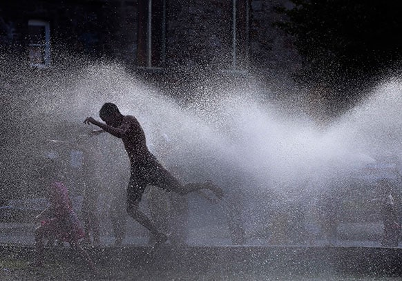 Kids cool off in the spray of an open hydrant on a hot evening in Lawrence, Mass. Area temperatures during the day reached into the 90s.
