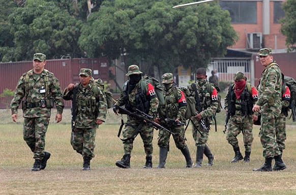 Soldiers, left and right, escort rebels of the National Liberation Army, ELN, who gave themselves up upon their arrival to a military base in Cali, Colombia.