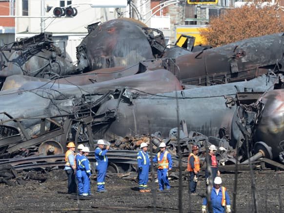 Emergency workers examine the aftermath of a train derailment and fire in Lac-Megantic, Quebec. Thirty-seven bodies have been recovered and another 13 people missing are still missinfg after the July 6, 2013, derailment.