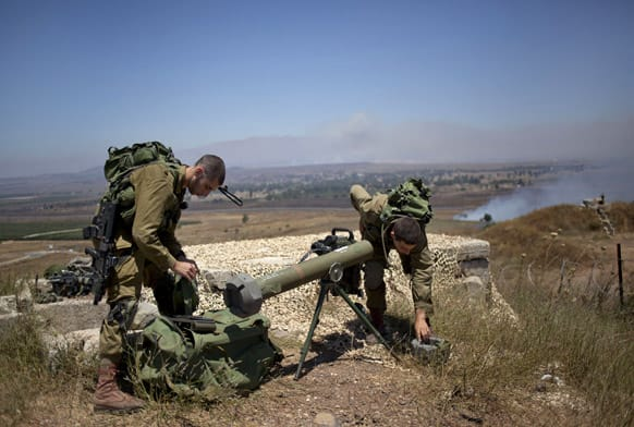 Israeli soldiers cover a rocket at the border with Syria on the Israeli controlled Golan Heights as smoke rises following explosions.