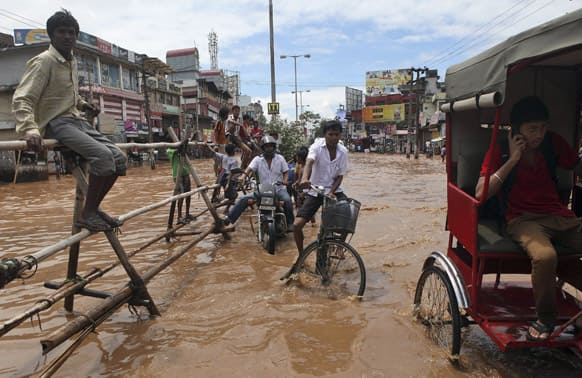 People move through a waterlogged street in Guwahati. Heavy showers flooded some areas in the city on Tuesday.