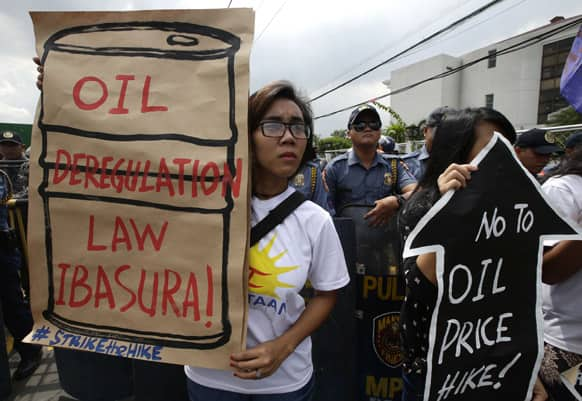 Riot police watch as protesters display placards during a rally outside an oil depot to protest another round of oil price increase implemented by the big three oil companies, in Manila, Philippines.