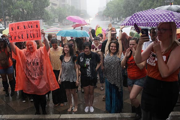 Abortion rights demonstrators rally outside of the State Capitol to protest recent legislation that could shut down all but five clinics and restrict abortion rights throughout the state in Austin, Texas.