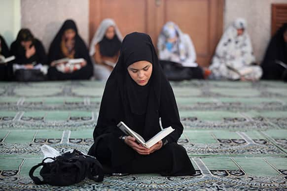 An Iranian woman recites verses from the Quran during the Muslim holy month of Ramadan at a mosque in Tehran, Iran.