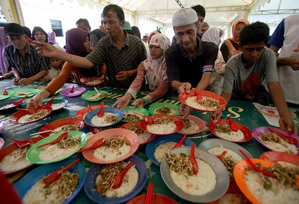 Officials prepare meals provided free for Muslim devotees to break their fast at a mosque in Medan, North Sumatra, Indonesia.