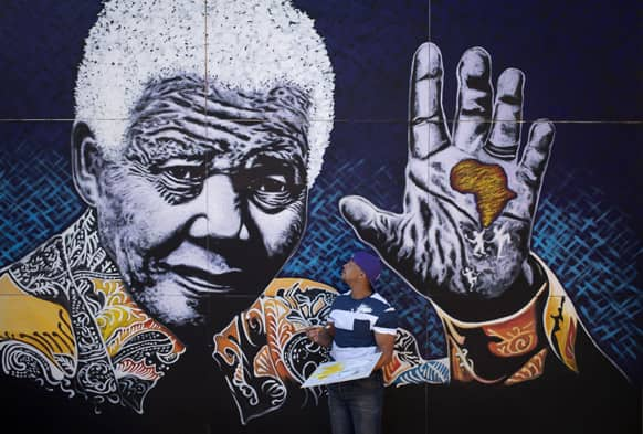 South African artist John Adams works on a giant acrylic-on-canvas painting of Nelson Mandela in the driveway of his house in a suburb of Johannesburg, South Africa.