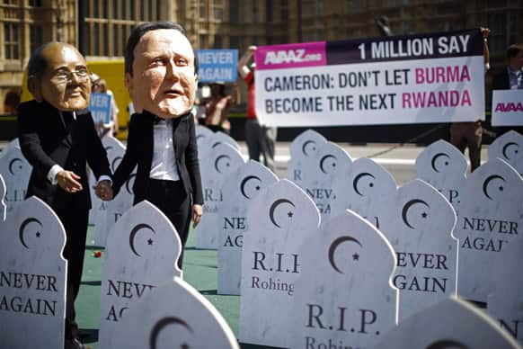 Campaigners supporting the `Avaaz, Burma Campaign UK` organization wear masks representing British Prime Minister David Cameron, right, and Myanmar`s President Thein Sein as they pose for photographs during a protest photocall outside the Houses of Parliament in London.