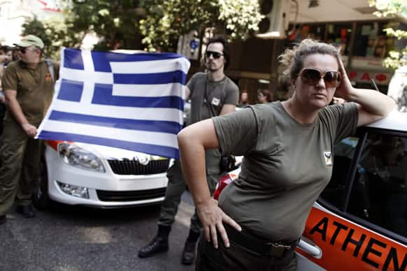Striking Municipal police officers hold a Greek flag during a protest against new austerity cuts that will affect thousands of public sector workers, outside the Greek Parliament in Athens.