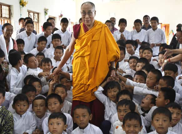 Tibetan spiritual leader the Dalai Lama poses for a photo with students of a Tibetan school after inaugurating its auditorium in Gurupura 210 kilometers (131 miles) southwest of Bangalore.