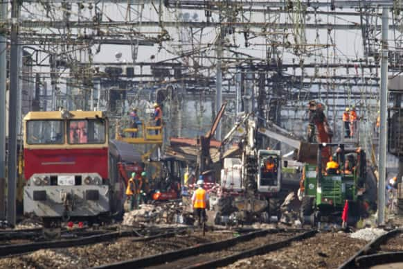Railway company employees work at a site of a train accident at a station in Bretigny sur Orge, south of Paris.