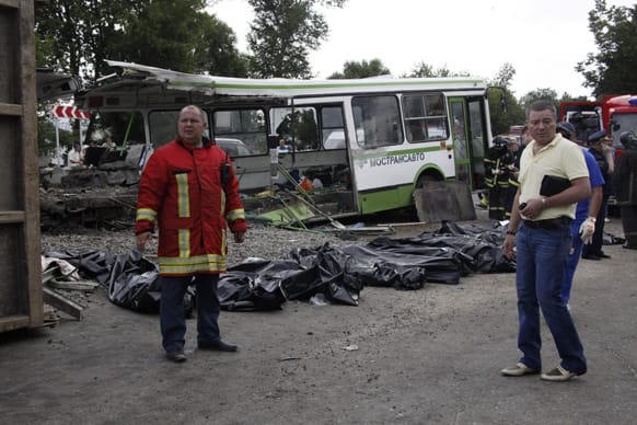 Bags containing victims of a crash involving a bus and a truck are laid at the site of the crash near Oznobishino, a settlement in the Moscow, Russia. Fourteen people are dead after a truck carrying concrete ran into a passenger bus in an outlying area of Moscow.