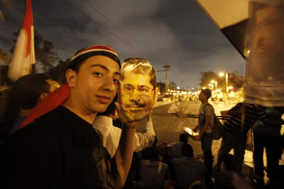 A supporter of Egypt`s ousted President Mohammed Morsi poses with a paper mask of Morsi as he and others face the Egyptian military soldiers near the presidential palace in Cairo, Egypt.