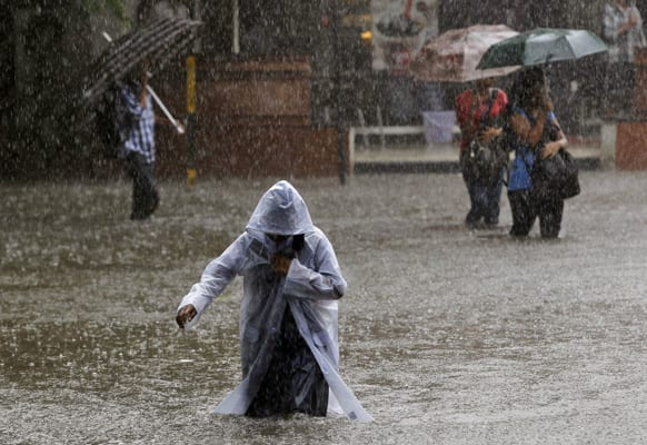 A girl wearing a raincoat wades through a flooded street as it rains in Mumbai.