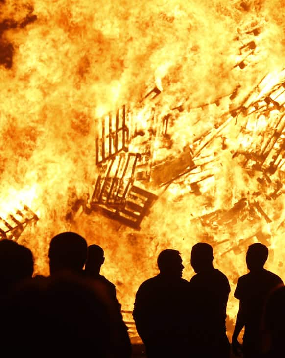Loyalists attend a bonfire in the Sandy Row area of Belfast, Northern Ireland. Hundreds of fires were set alight Thursday as loyalists celebrate the July 12, remembering the defeat of the Catholic King James, by the Protestant William of Orange in 1690.