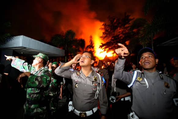 Police officers and soldiers give orders to others as they are deployed outside Tanjung Gusta prison that was partially set ablaze by inmates during a prison riot in Medan, North Sumatra, Indonesia.