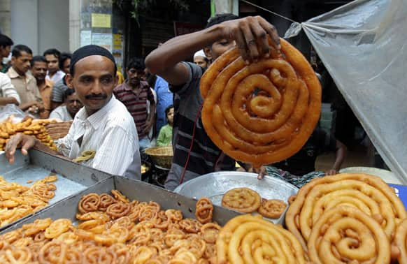 A Bangladeshi vendor displays traditional food items as Muslims crowd the area to break their fast on the first day of Ramadan in Dhaka.