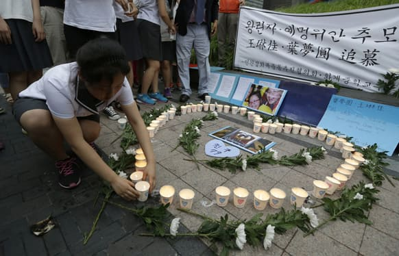 South Korean students light candles during a candlelight vigil to mourn the deaths of the two Chinese victims who died in a Asiana Airlines plane crash in San Francisco, in Seoul, South Korea.