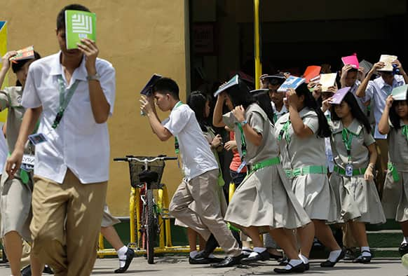 Students of Sta. Elena High School cover their heads with their notebooks as they rush out of their campus to simulate an earthquake during a drill to coincide with the ongoing Asian Crisis Management Conference at Marikina city east of Manila, Philippines.